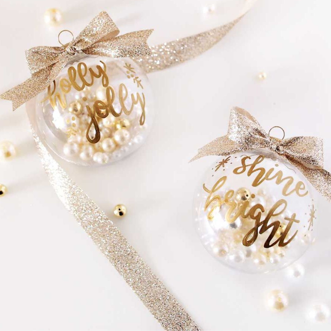 Easy handmade Christmas ornaments - LOVE all these Ideas for Decorating Clear Christmas Balls - Clear Christmas tree balls filled with pearls, fun Holiday sayings painted on in pretty lettering, and topped with metallic ribbon bows.
