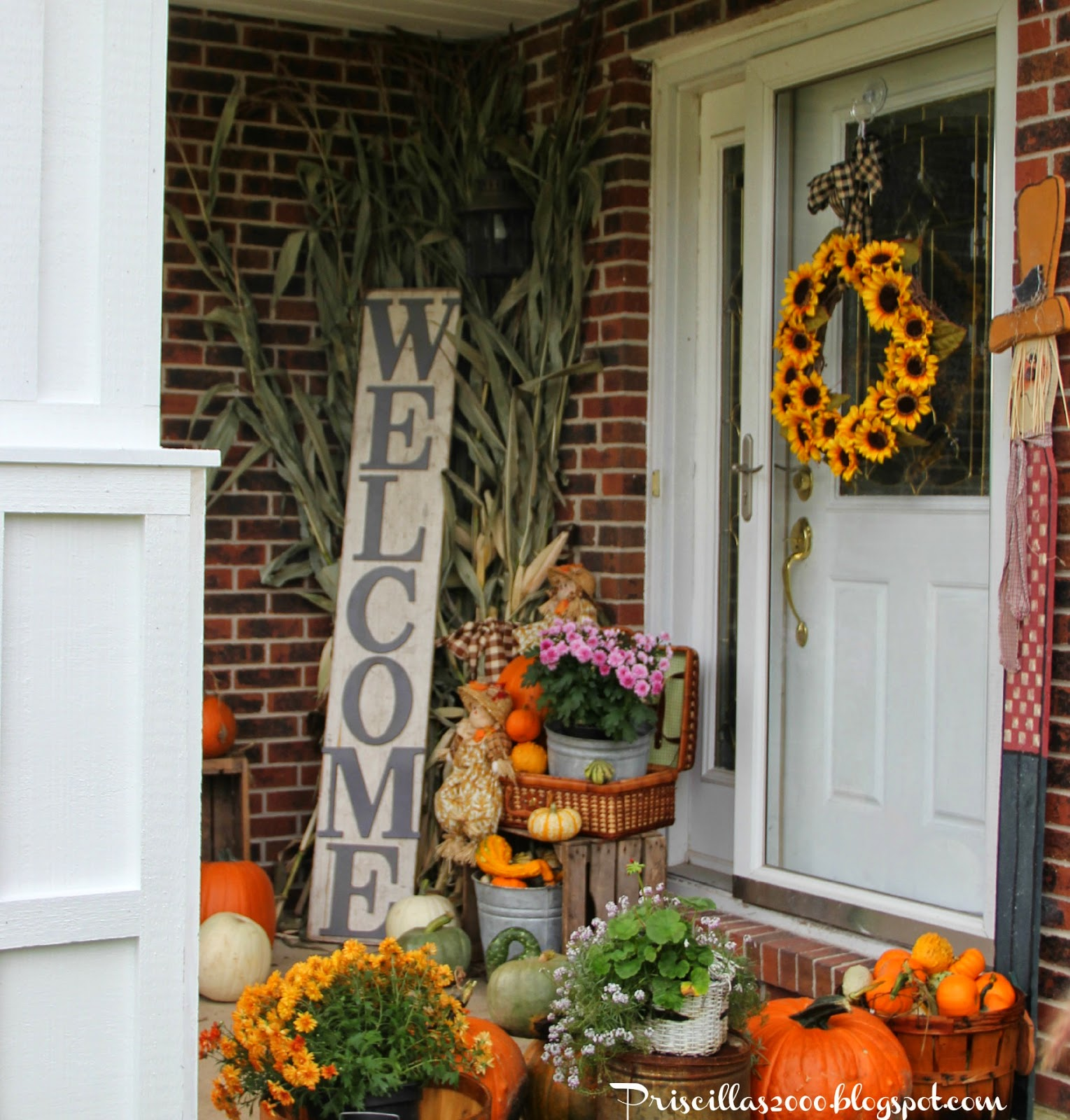 Beautiful Fall front porch with pumpkins, mums, and a sunflower wreath.