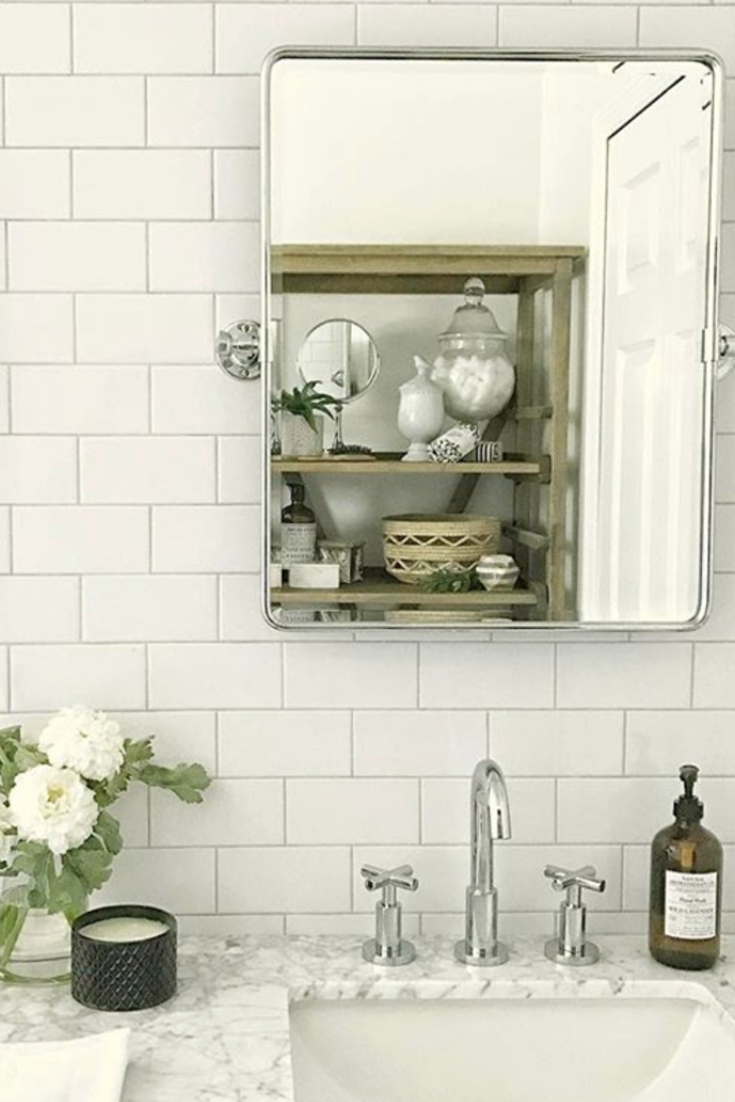 Subway tile bathroom wall idea - love the look of this bathroom makeover project after using subway tile on the wall behind the mirrors.