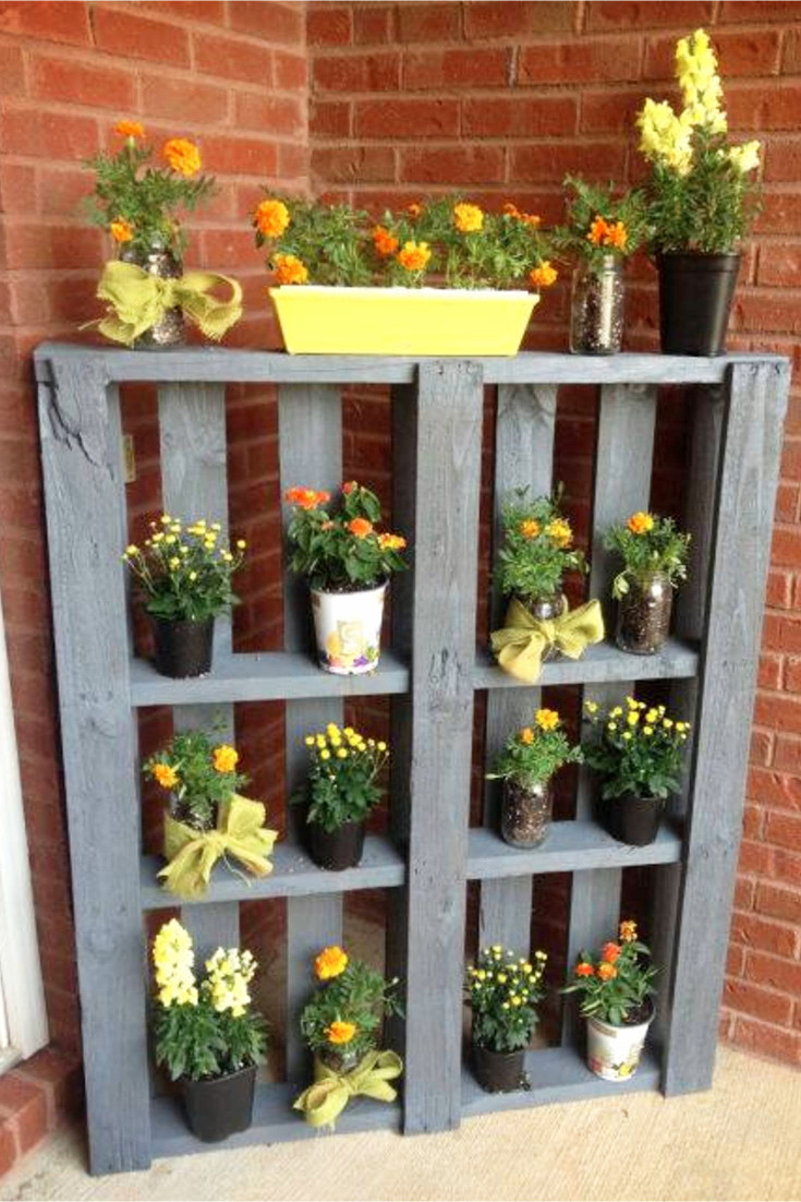 This is pretty yet such an easy DIY pallet project!  Take an old pallet, paint the wood and turn it on it's side to use as an outdoor flower shelf for your potted plants.